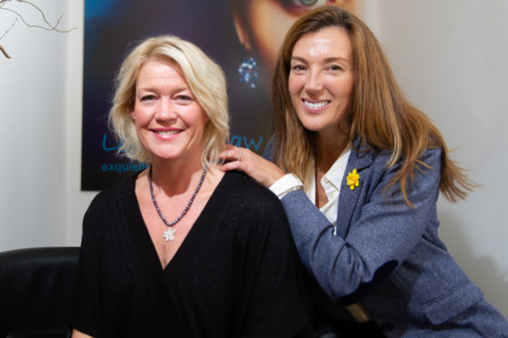 Elaine Sommerville wearing one of the daffodil inspired pieces crafted by Lorraine Law Jeweller and Petra Macmillan of Marie Curie.
