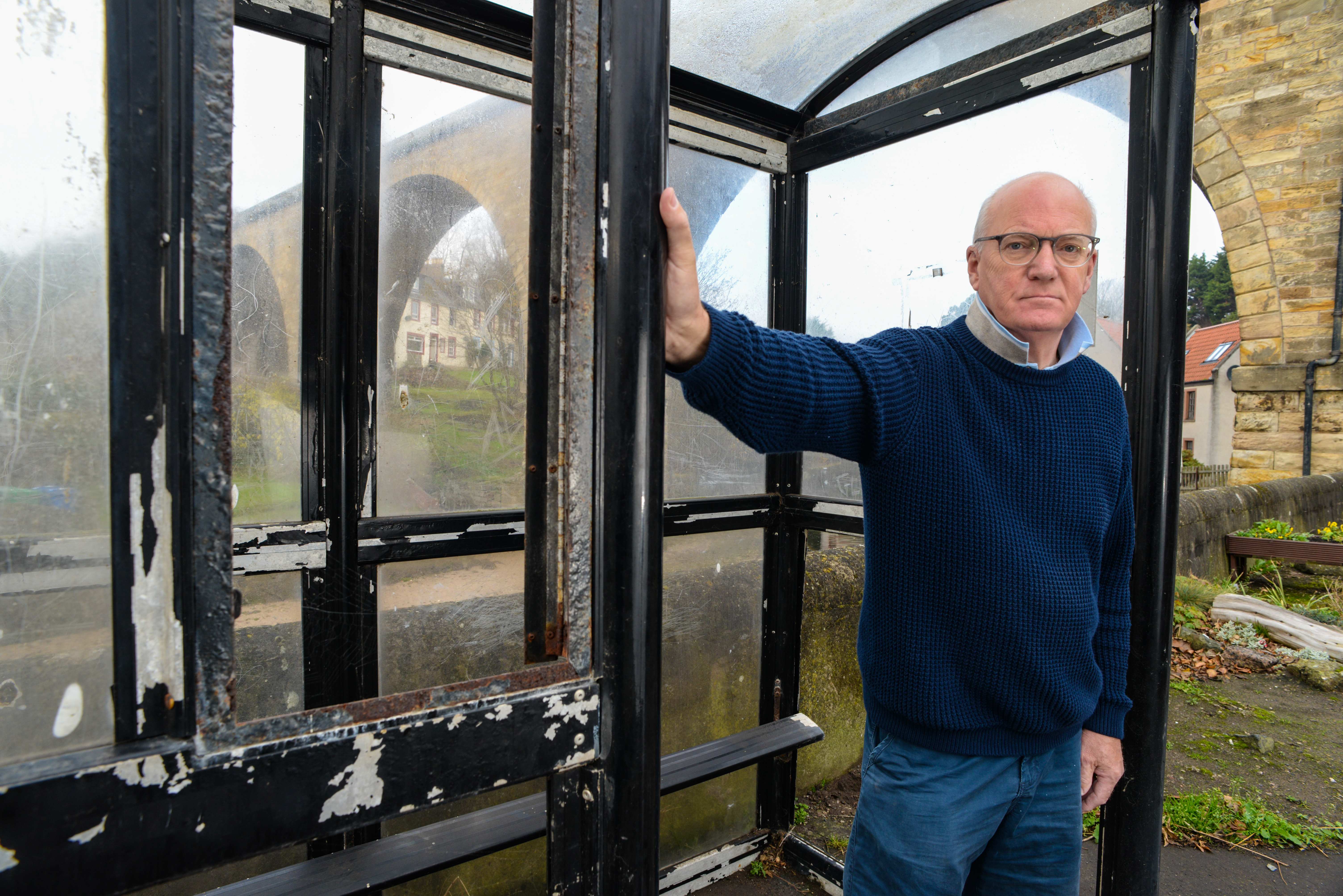 Local resident Eddie Hagan standing in the vandalised bus-stop which he has been campaigning to have repaired for over a year. Lower Largo.