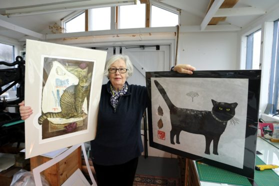 """Sheila MacFarlane with two of Barbara Robertson's pieces of artwork entitled """"Signs of Leo"""" and """"Winter Cat""""."""