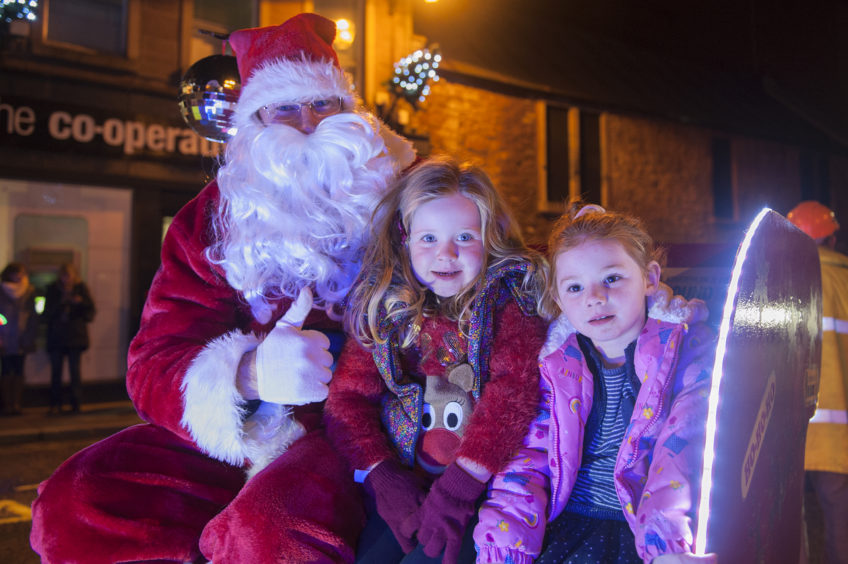 l to r, Santa, Lilly Sinclair and Anna Beckers at the Kirriemuir Christmas light switch on, 24 November 2018