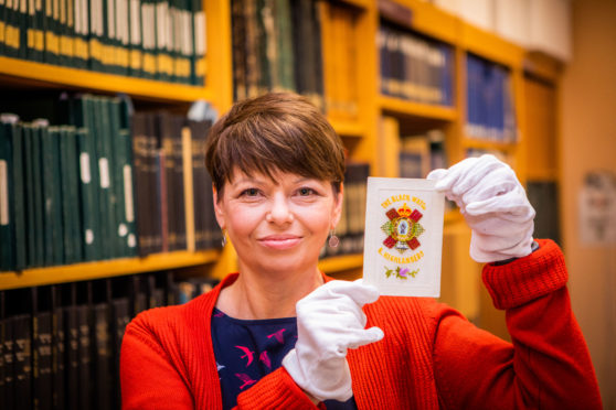 Archivist Lorna Westwater with one of the silk embroidered First World War postcards - a Black Watch design.