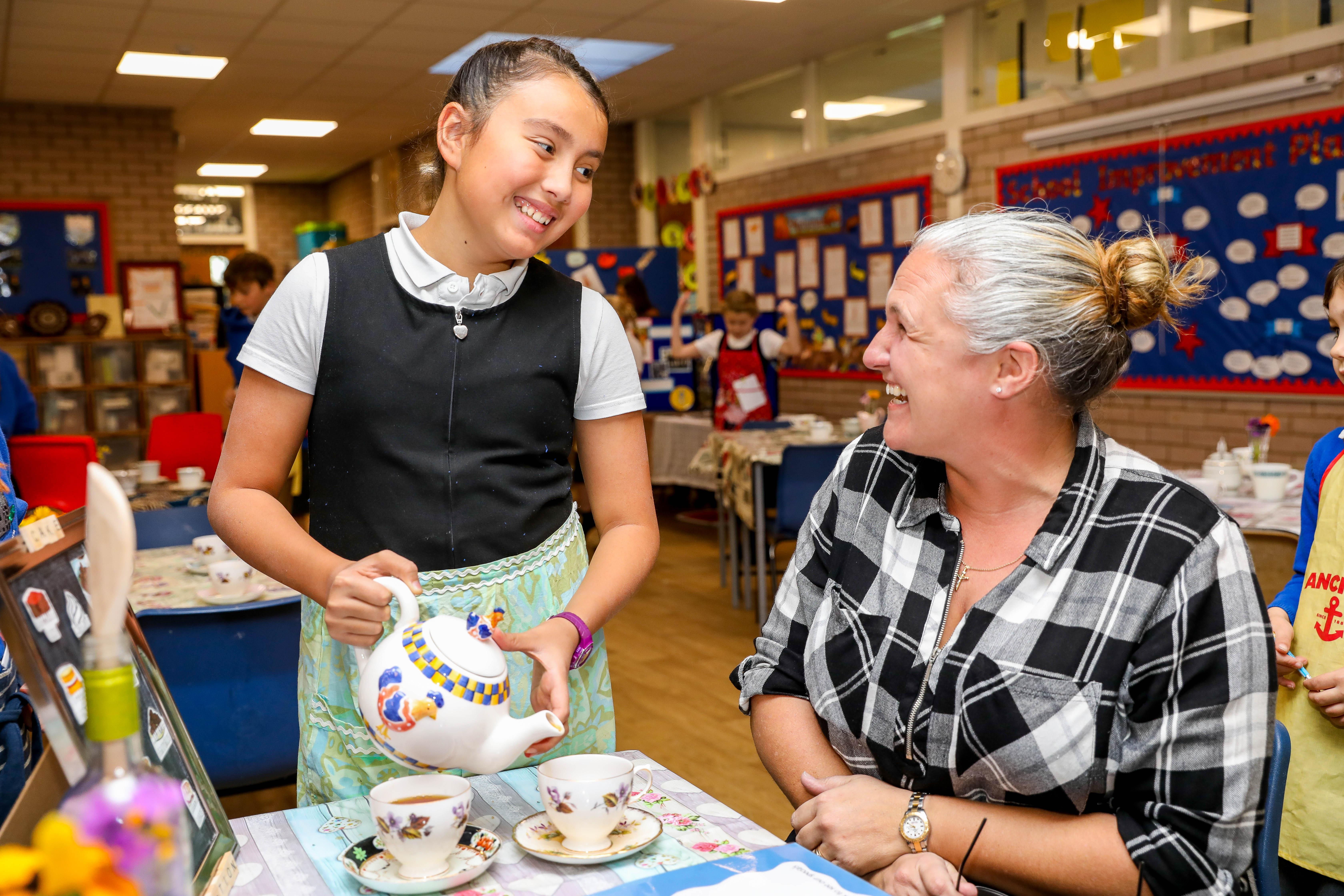 Natalie Fraser serves a cup of tea to local resident Meg MacKinnon.