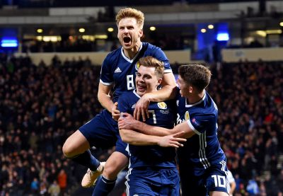 Stuart Armstrong (top) celebrates with James Forrest and Ryan Christie.