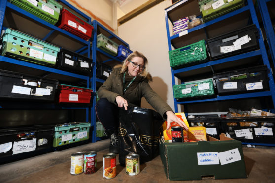 Perth and Kinross food bank coordinator Eleanor Kelleher preparing a parcel.