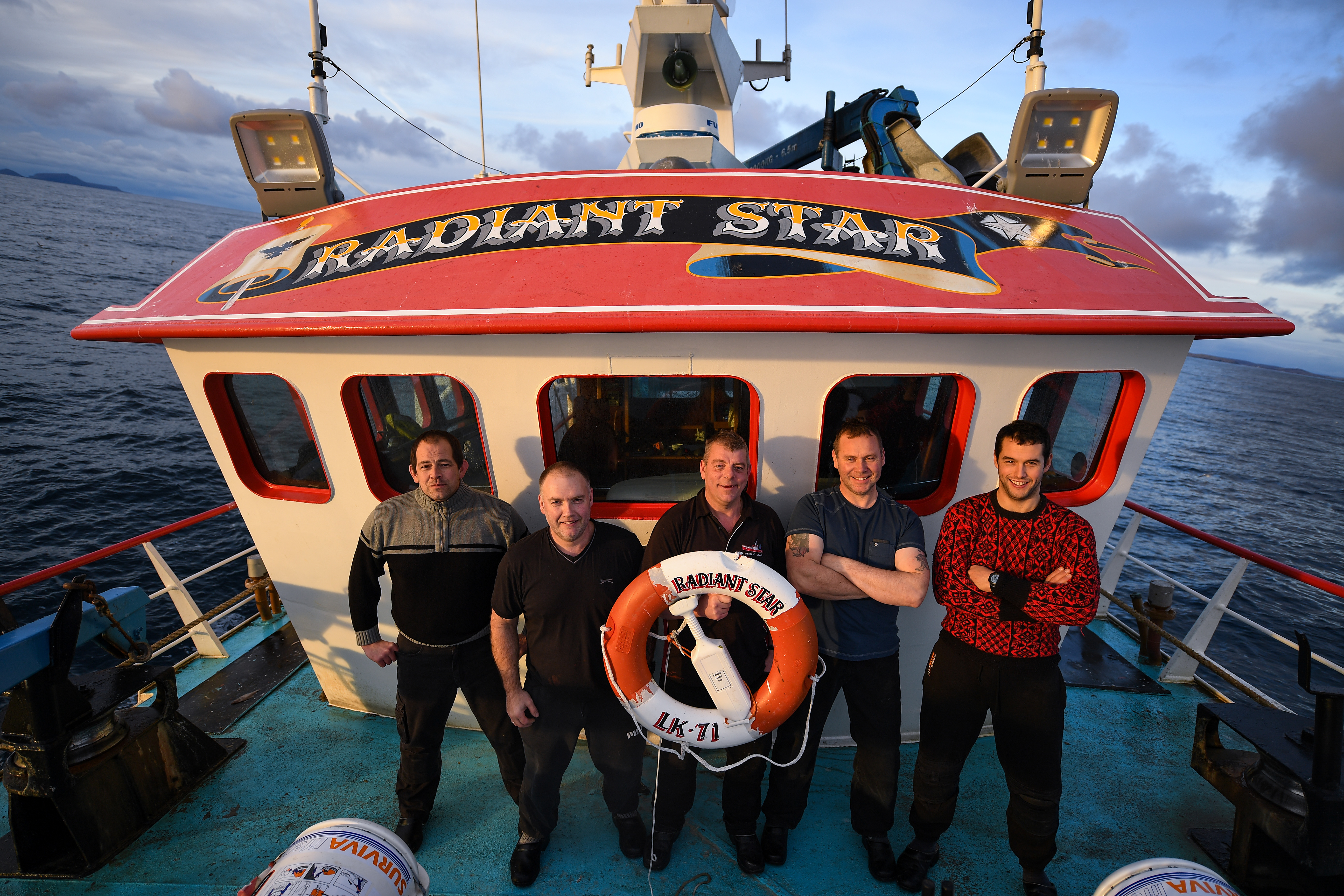 Jimmy Reid,Ian Couper, Victor Laurenson,Victor Duncan and Marven Inkster crew members of the Radiant Star, stand on deck during a days fishing in the North Sea on December 5, 2018 in Shetland, Scotland.