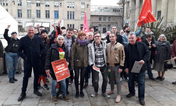 """Union members and former Brassica employees celebrate their """"small victory"""" outside the City Chambers on Thursday."""