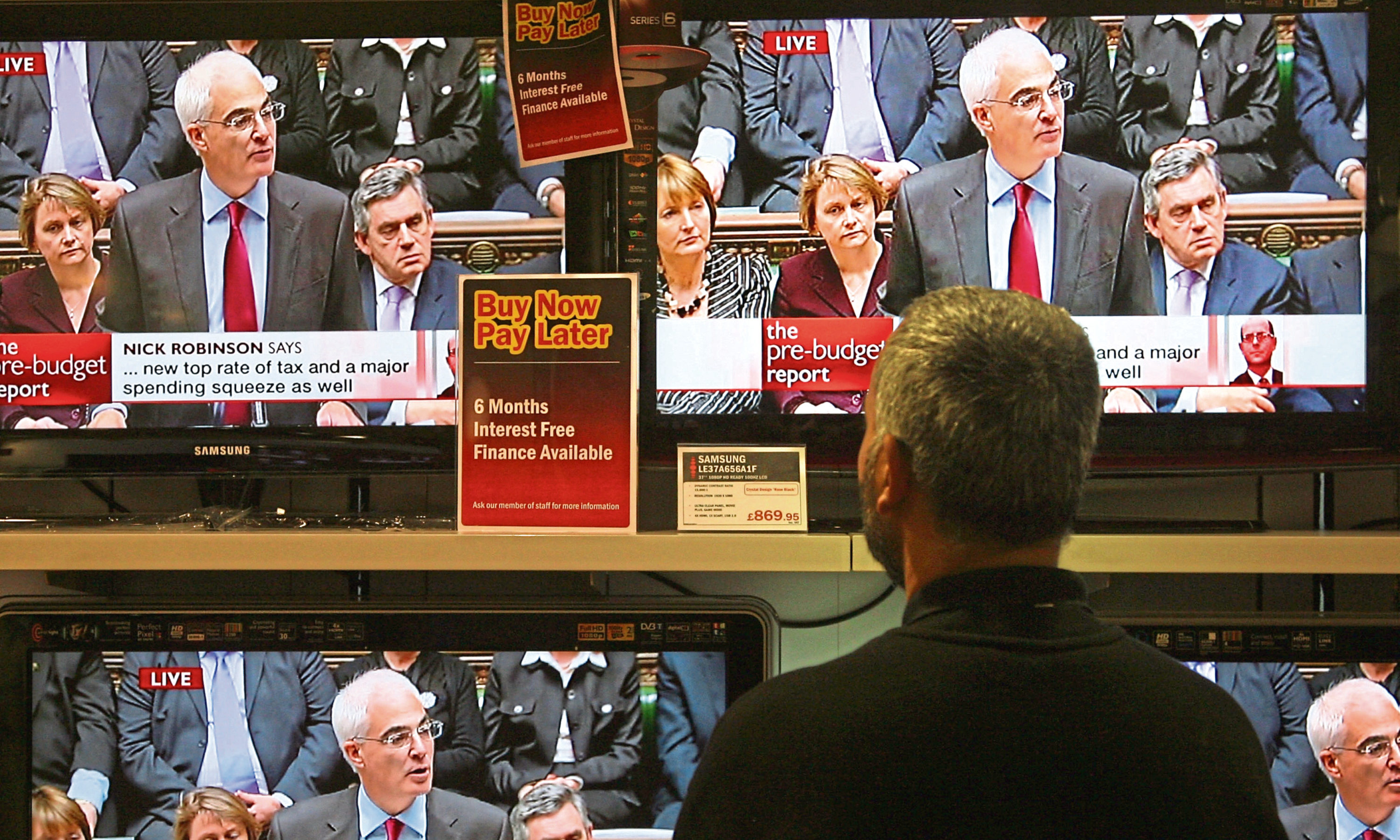 Albert Ram, a salesman at Ask electrical retailers on Tottenham Court Road, cleans the screens of televisions showing the Chancellor of the Exchequer, Alistair Darling, live in Parliament delivering his Pre-Budget Report on November 24, 2008 in London, England.
