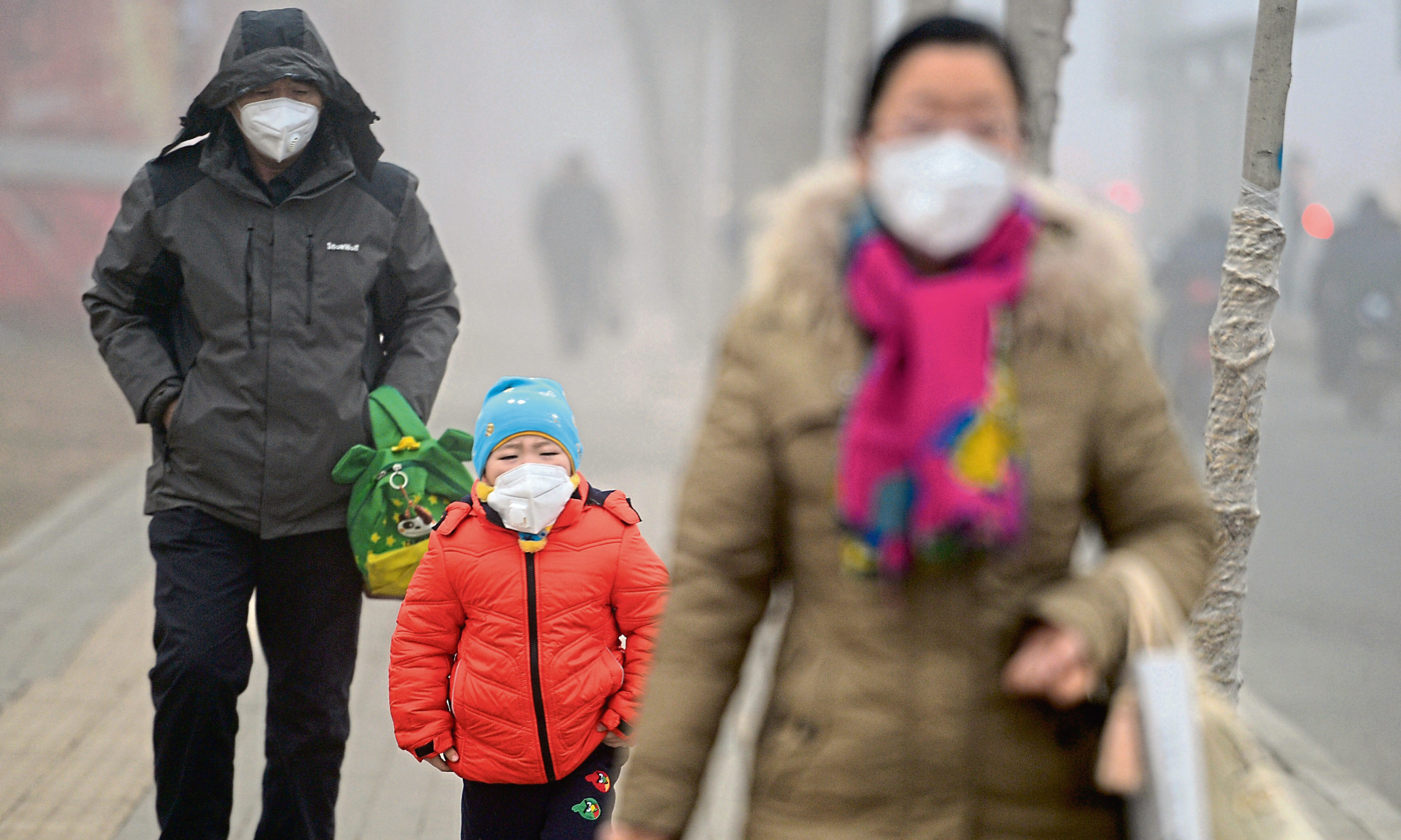 Citizens wearing masks walk on the road which is blanketed by heavy smog on January 5, 2017 in Jinan, Shandong Province of China.