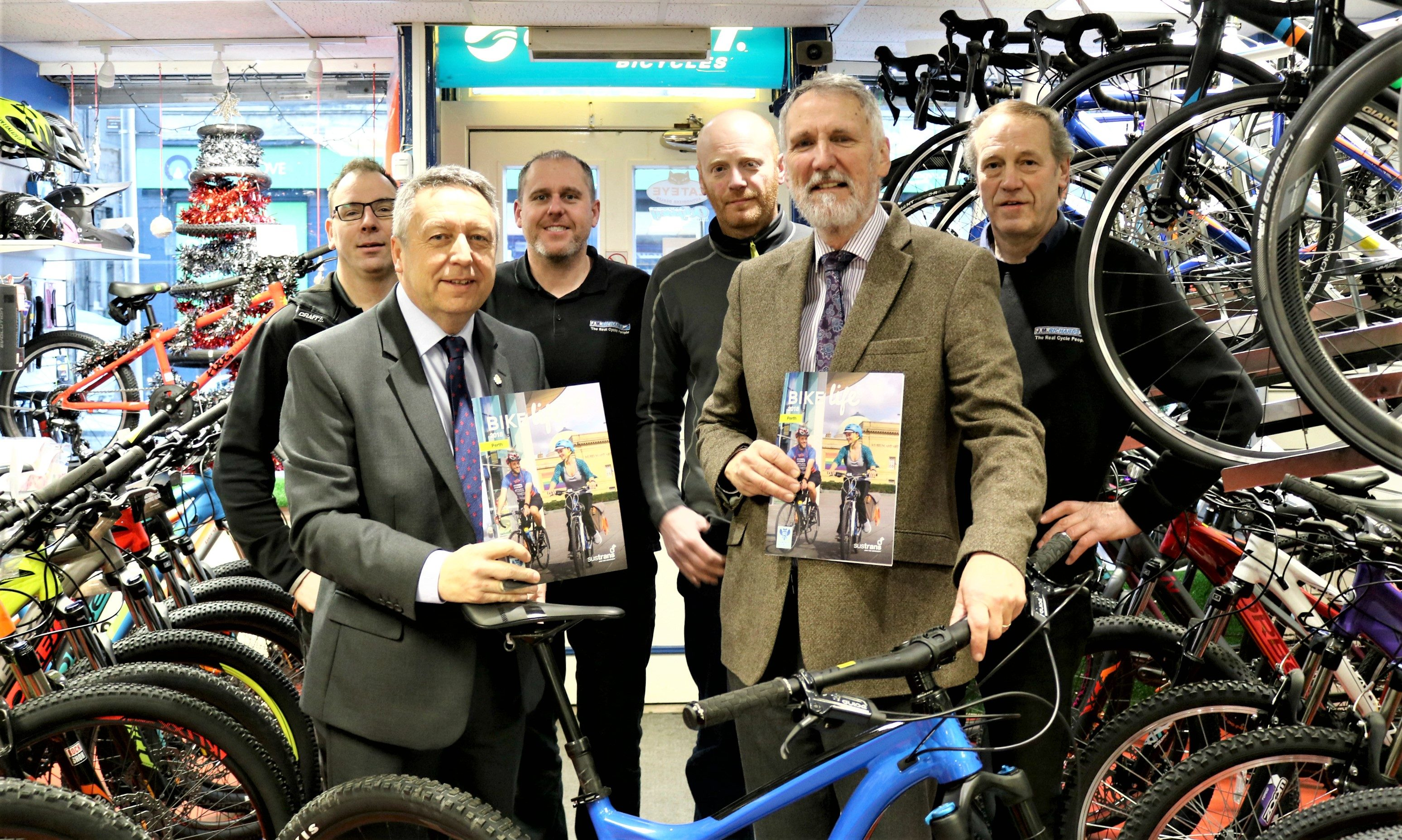 Councillor Lewis Simpson (front right holding Bike Life report) and Councillor Angus Forbes with staff at family-run cycle shop J. R. Richards, George Street, Perth.