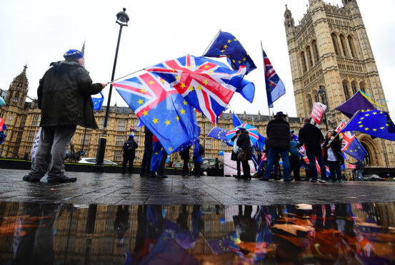 Anti-Brexit campaigners with Union and European Union flags outside the House of Commons in London.
