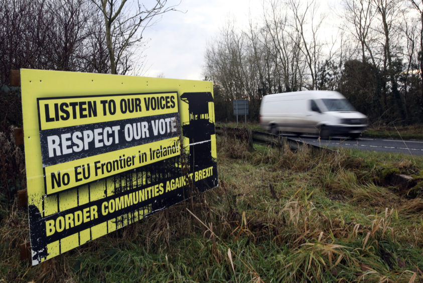 A poster against a hard border stands on the border between Northern Ireland and the Republic of Ireland near the town of Derrylin, Northern Ireland, Wednesday, Dec. 12, 2018. With compromises on both sides in the Brexit deal, Britain and the EU managed to reach agreement on many contentious issues. But one has proved intractable: the border between Northern Ireland and Ireland, which will be the U.K.'s only land border with the EU after Brexit.