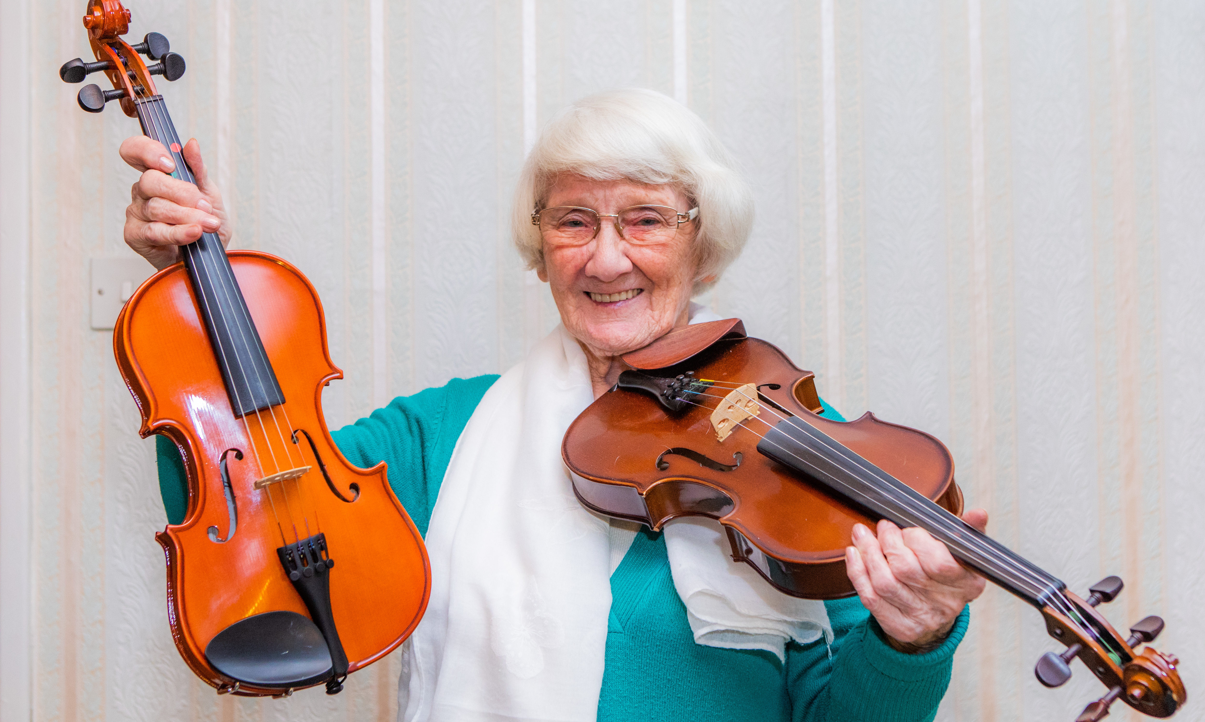Jean Ferguson at home with the two fiddles