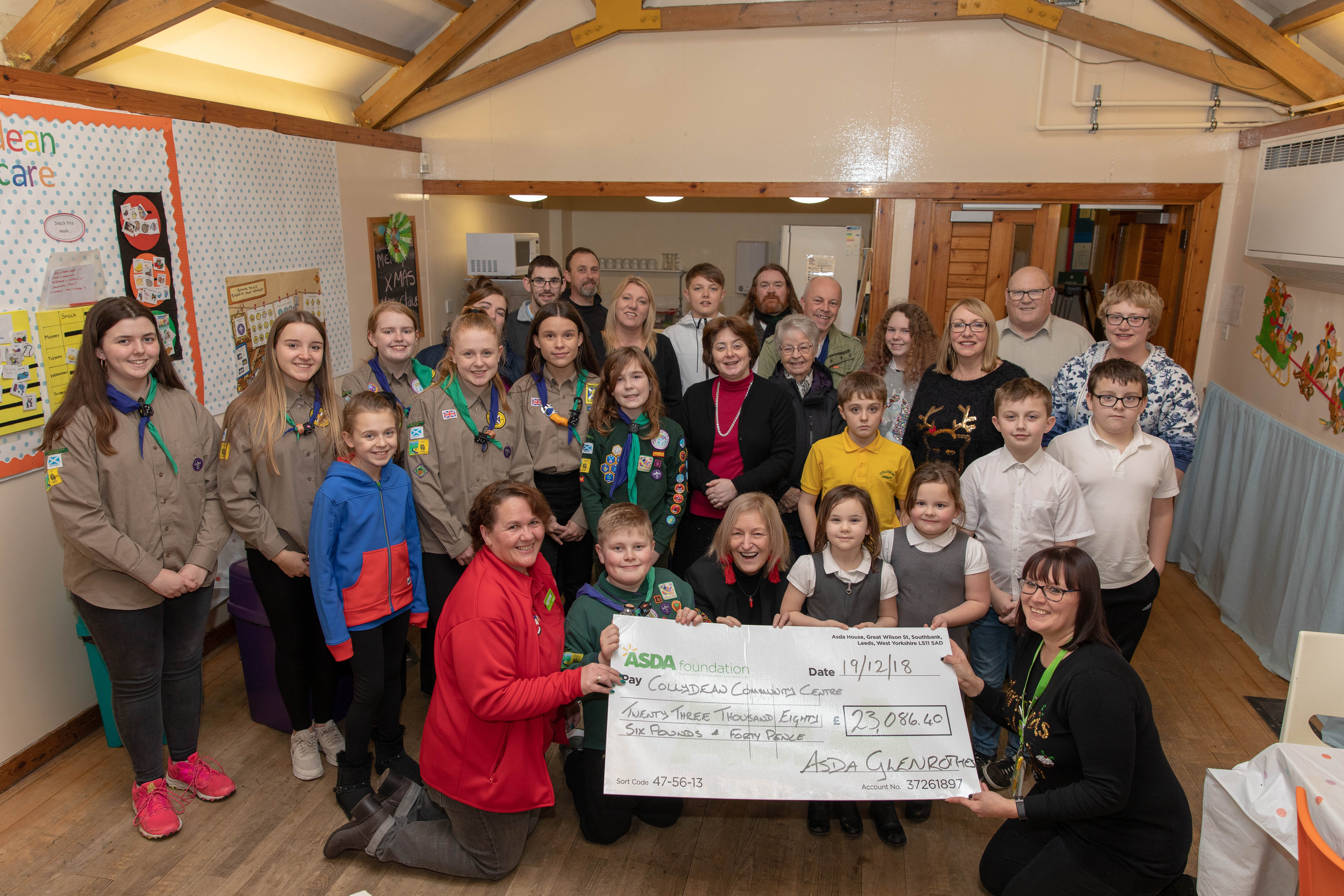 Avril Dullea presents cheque to Rose Duncan from the cafe attended by 89th North Glen Scouts group and local councillors and people who will benefit from the donation