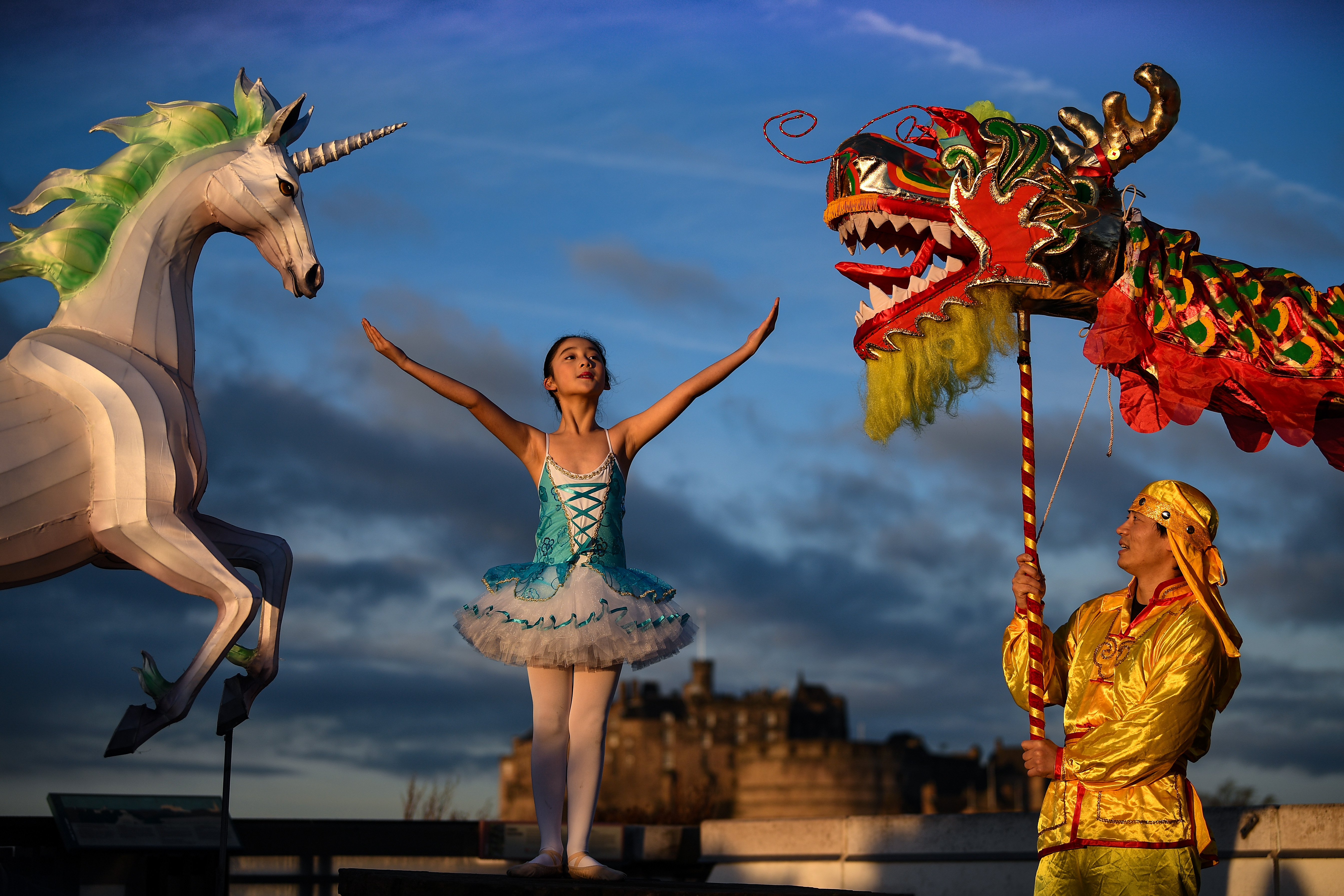 Nina Sun stands beside a unicorn lantern and a Chinese dragon during the launch of the Chinese New Year Edinburgh festival.