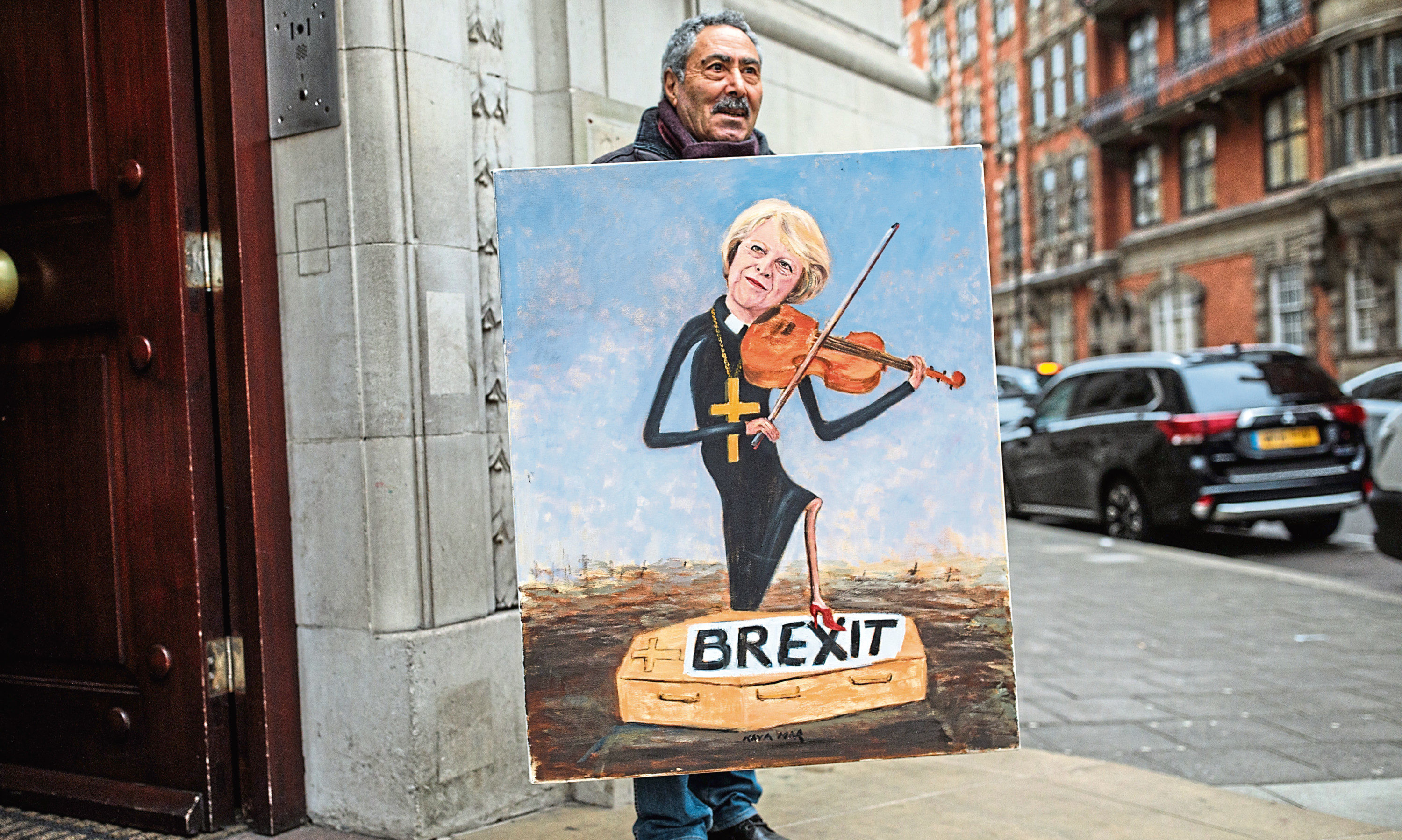 Political artist Kaya Mar stands with his painting depicting Prime Minister Theresa May playing a violin outside Millbank Studios in Westminster on January 16, 2019 in London.