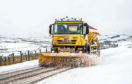 A gritter lorry clears a road.