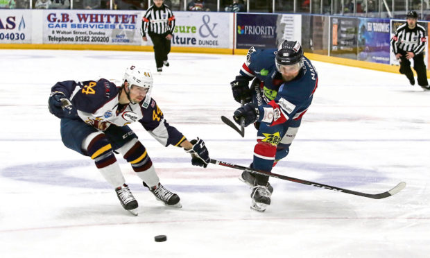 Dundee Stars' Matt Marquardt gets his shot away before Flames Jesse Craige can close him down.