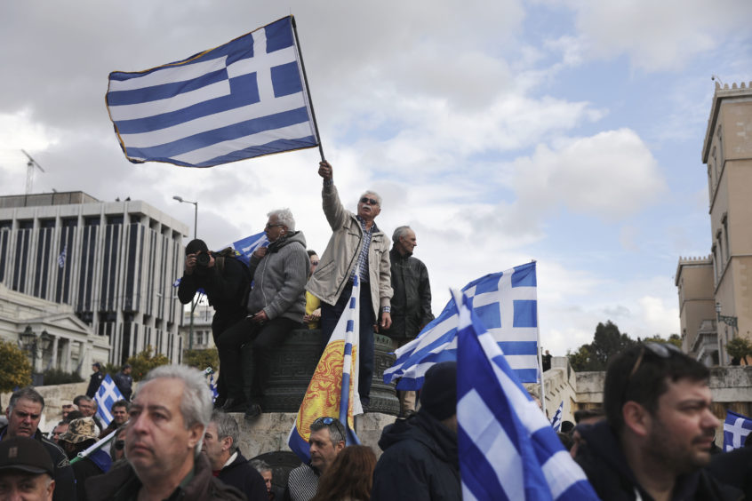 Demonstrators wave Greek flags outside parliament during a rally in Athens.
