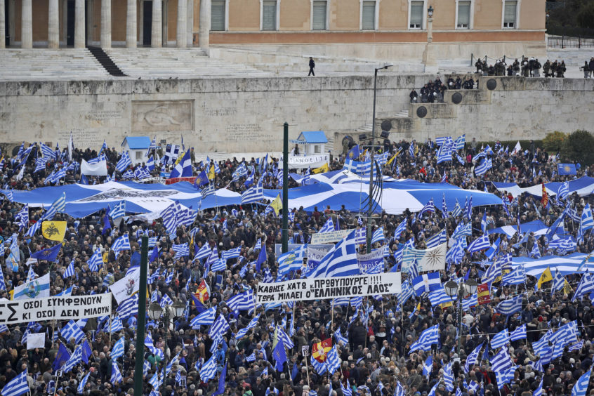 Demonstrators hold Greek flags during a rally outside parliament in Athens.