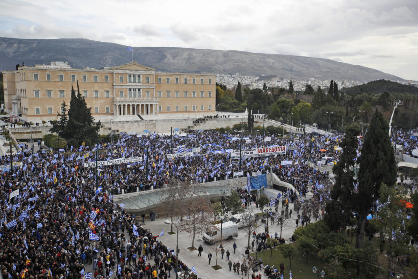 Protestors opposing to North Macedonia's name wave Greek flags outside parliament in Athens.