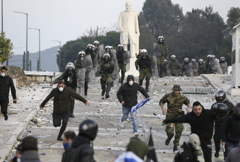 Greek riot police chases demonstrators during clashes.