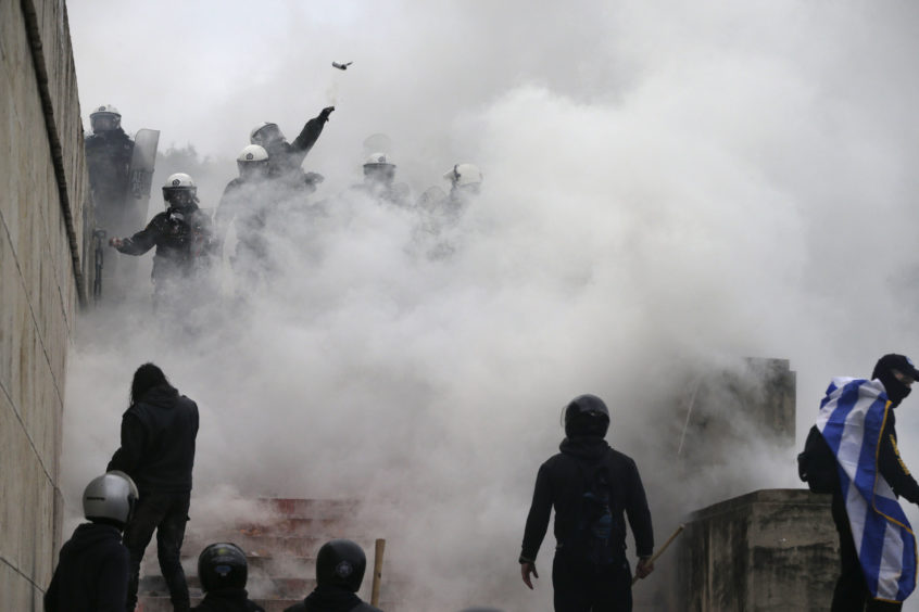 A riot police throws a tear gas grenade during clashes outside parliament in Athens.
