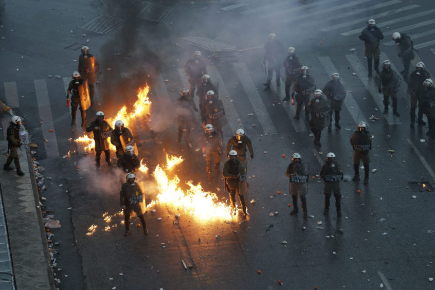 A molotov cocktail explodes next to Greek riot police during clashes after a rally in Athens.