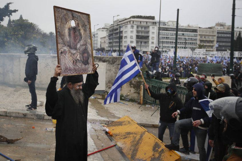 An Orthodox monk holds a representation of the Virgin Mary and child during a clashes in Athens.