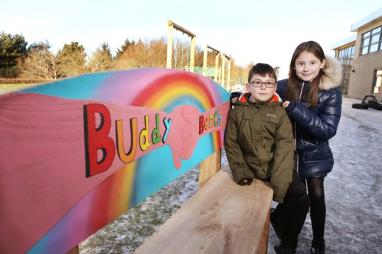 Pupils Lilli-Jane Buchanan and Liam Wood next to the buddy benches.