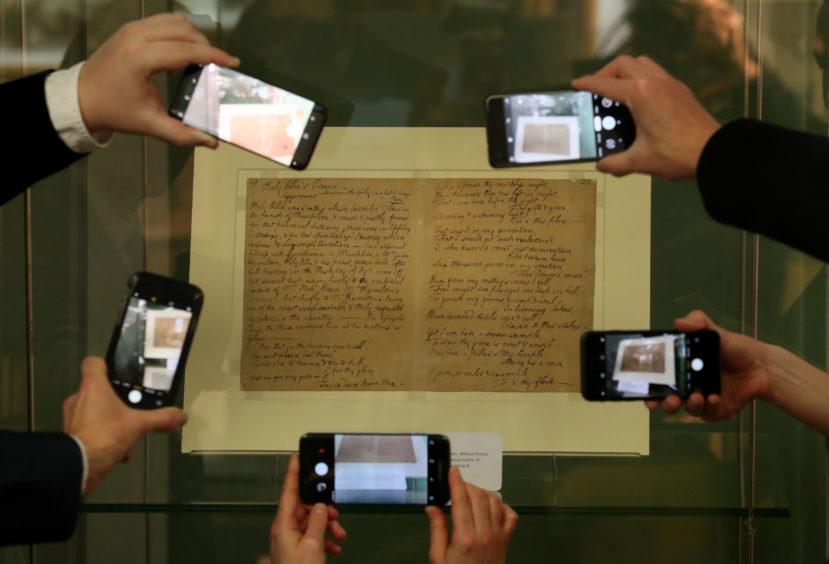 Visitors take a photograph on their phones of Holy Willie's Prayer (1785). This is a rare manuscript containing some of the most provocative social commentary by Robert Burns, which is on show for one day only at the National Library of Scotland at Kelvin Hall in Glasgow, to mark the anniversary of his birth on January 25, 1759.