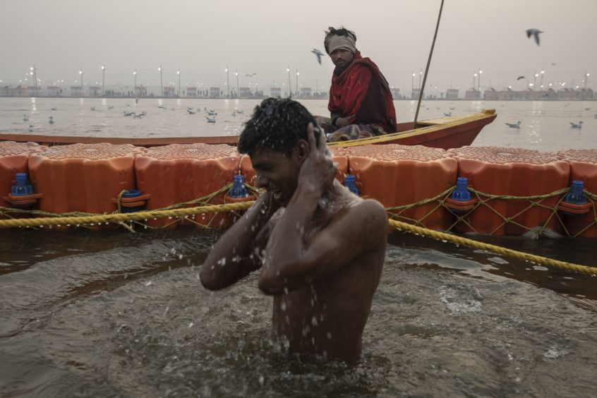 An Indian Hindu devotee takes a holy dip at Sangam, the confluence of the rivers Ganges, Yamuna and mythical Saraswati, during the Kumbh Mela festival in Allahabad, India.