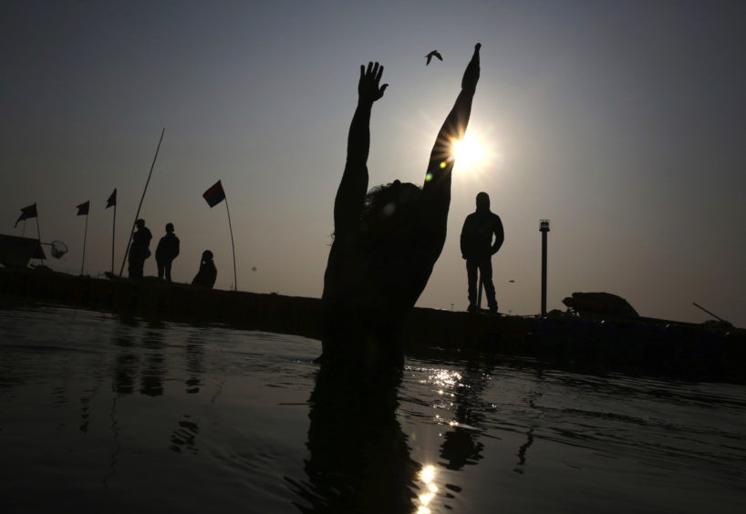 A Hindu devotees takes ritualistic dips at Sangam during Kumbh Mela or Pitcher festival at Prayagraj Uttar Pradesh state, India. The Kumbh Mela is a series of ritual baths by Hindu holy men, and other pilgrims at Sangam, the confluence of three sacred rivers the Yamuna, the Ganges and the mythical Saraswati that dates back to at least medieval times.