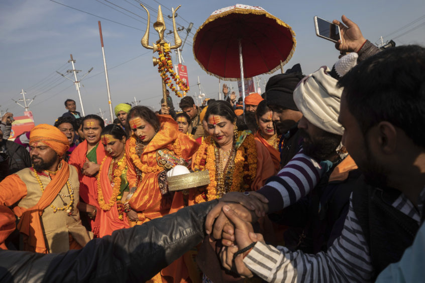 "Laxmi Narayan Tripathi, center left, a transgender activist and founder of the ""Kinnar Akhara"" monastic order arrive with other members of the order for a spiritual-cleansing dip on the auspicious Makar Sankranti day during the Kumbh Mela festival in Prayagraj, Uttar Pradesh state, India. Kinnars celebrated their inclusion at Kumbh as a victory, but their greater acceptance by Hinduism's most powerful leaders, in the religious and political spheres, remains to be seen. Unlike other akharas, which are only open to Hindu men, Kinnar, founded in 2015, is open to all genders and religions."