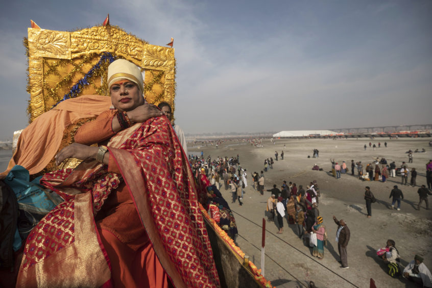 "A member of the ""Kinnar Akhara"" monastic order sits on a carriage during a procession on auspicious Makar Sankranti day during the Kumbh Mela festival in Prayagraj, Uttar Pradesh state, India. Unlike other akharas, which are only open to Hindu men, Kinnar, founded in 2015, is open to all genders and religions. On the Kumbh's first bathing day, transgender activist Laxmi Narayan Tripathi led a train of 21 tractor chariots from their tent camp to the bathing ghats with devotees following on foot as observers showered them with flower petals."