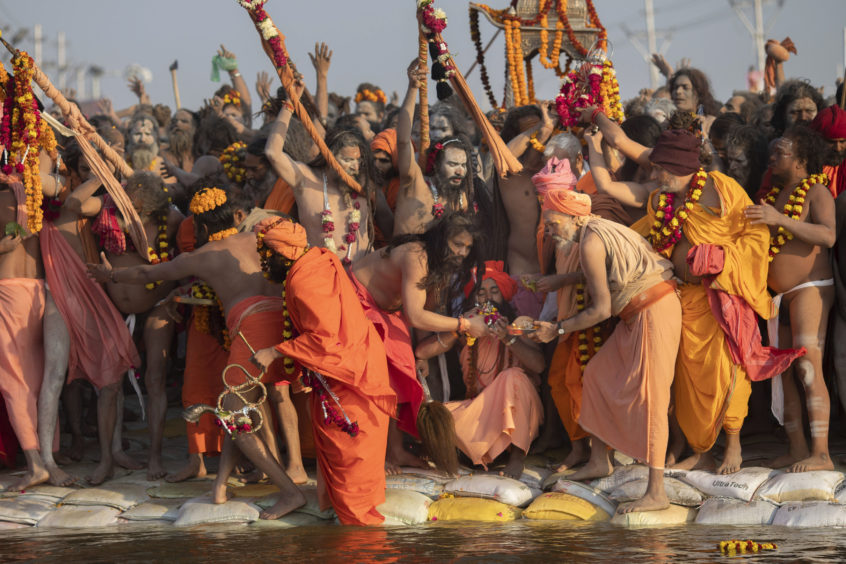 "Hindu holy men from one of the ancient and most orthodox akharas ""Juna akhara"" take a dip on auspicious Makar Sankranti day during the Kumbh Mela festival in Prayagraj, Uttar Pradesh state, India. The Juna Akhara is the only monastic order to have accepted the newly formed Kinnar Akhara, led by transgender activist Laxmi Narayan Tripathi. Unlike other akharas, which are only open to Hindu men, Kinnar, founded in 2015, is open to all genders and religions."