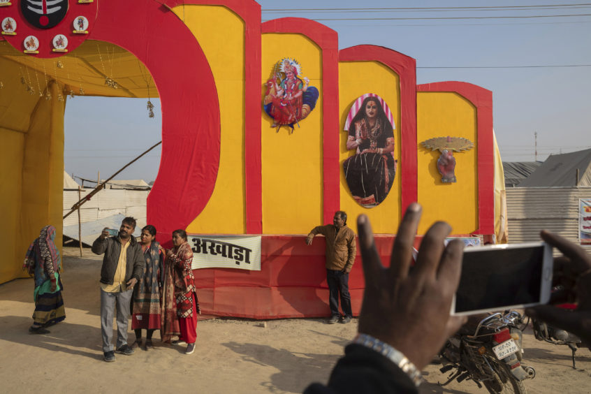 "Hindu devotees take snapshots by the entrance to ""Kinnar akhara,"" a monastic order formed by Laxmi Narayan Tripathi, who is among India's best-known transgender activists, during the Kumbh Mela festival in Prayagraj, India. The Kinnars tent camp on the edge of the festival grounds is adorned with Ardhanari, the androgynous composite image of the Hindu god Shiva and his consort Parvati, that religious scholars date to the 1st century. Tripathi is trying to break into the male-dominated world of Hinduism's high priests gathered this month in the north Indian city of Prayagraj on the Ganges river for the weeks-long Kumbh Mela festival, where tens of millions of Hindus travel every three years to take a holy dip."