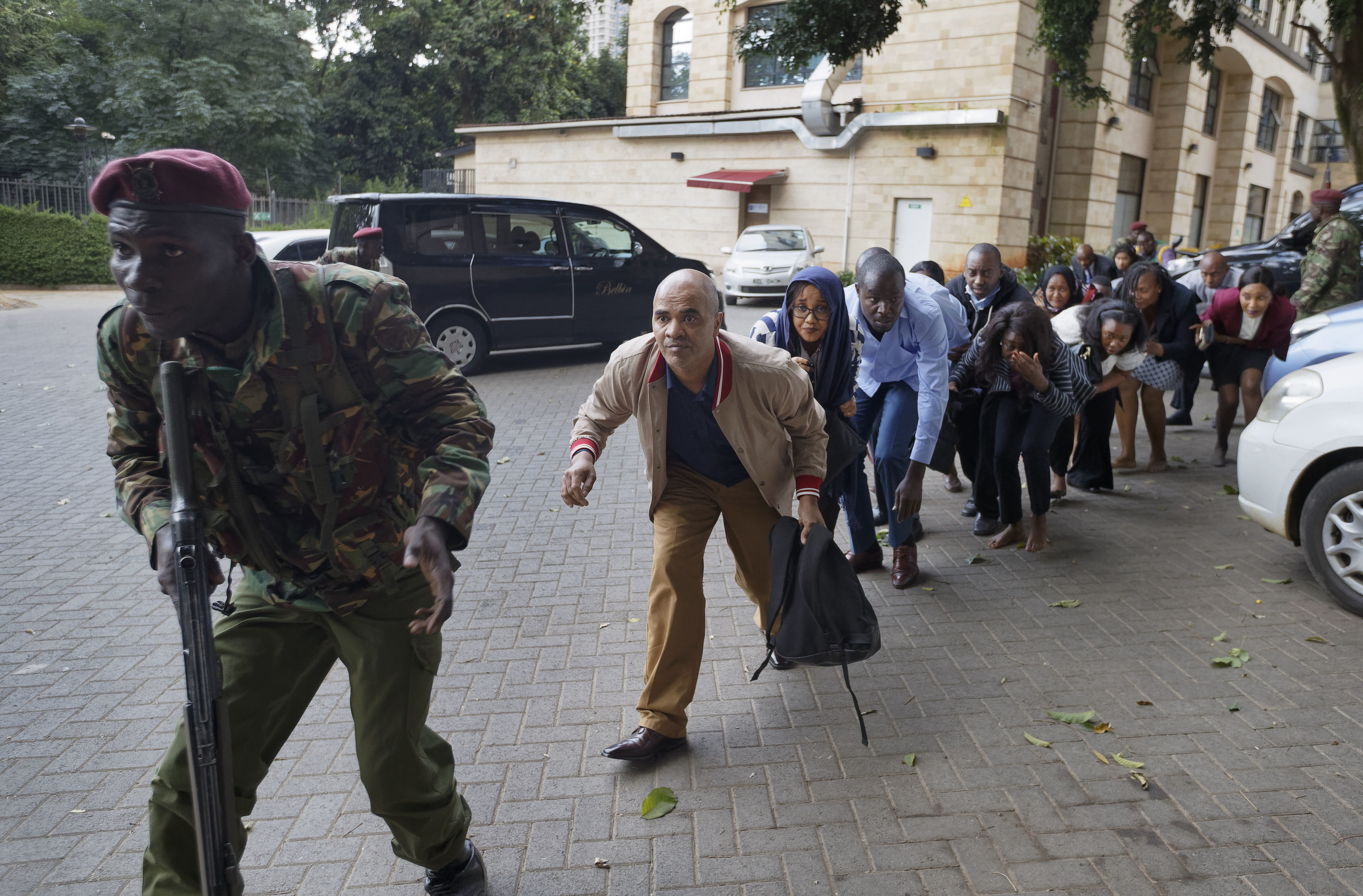 Civilians who had been hiding in buildings flee under the direction of a member of security forces at a hotel complex in Nairobi,. Terrorists attacked an upscale hotel complex in Kenya's capital Tuesday, sending people fleeing in panic as explosions and heavy gunfire reverberated through the neighborhood.