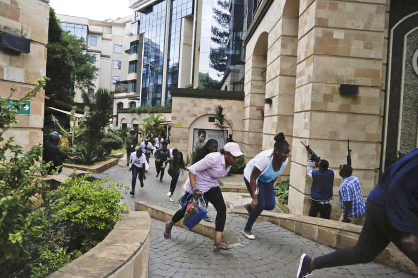 Civilians flee as security forces aim their weapons at a hotel complex in Nairobi.