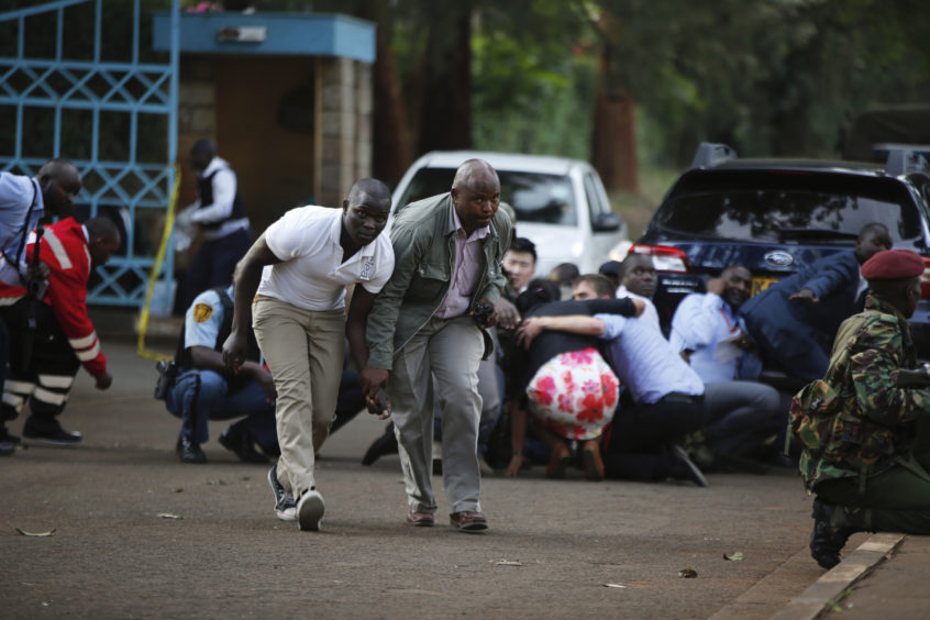 People take cover after an attack on a hotel, in Nairobi.