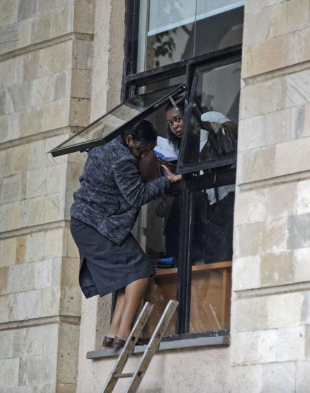 Civilians flee through a window at a hotel complex in Nairobi, Kenya Tuesday.