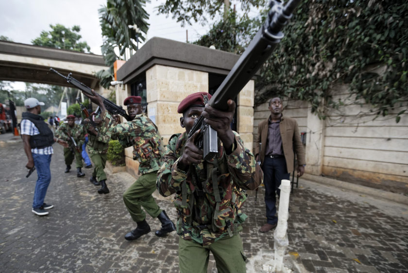 Kenyan security forces aim their weapons up at buildings as they run through a hotel complex. Terrorists attacked an upscale hotel complex in Kenya's capital Tuesday, sending people fleeing in panic as explosions and heavy gunfire reverberated through the neighborhood.
