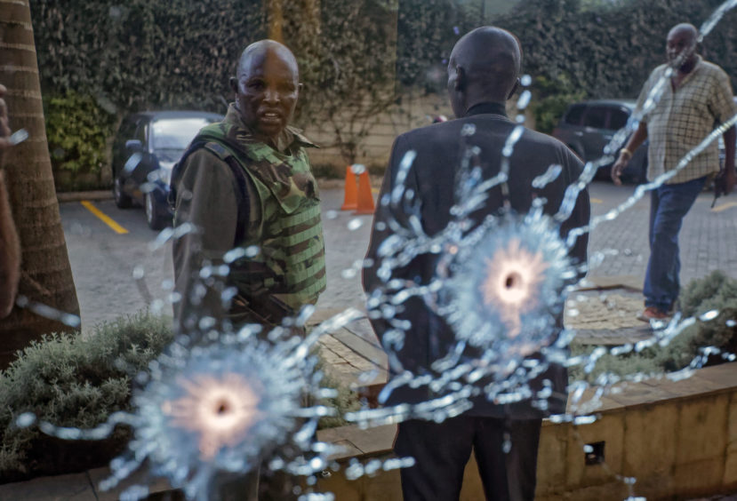 A member of the security forces is seen reflected in a window as he looks at bullet-holes, at a hotel complex in Nairobi, Kenya Tuesday, Jan. 15, 2019. Terrorists attacked an upscale hotel complex in Kenya's capital Tuesday, sending people fleeing in panic as explosions and heavy gunfire reverberated through the neighborhood.