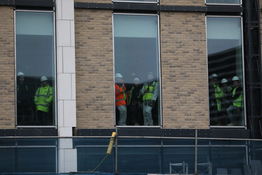 Workers sneek a peak from Site 6 opposite the V&A for the arrival. Kris Miller / DCT Media