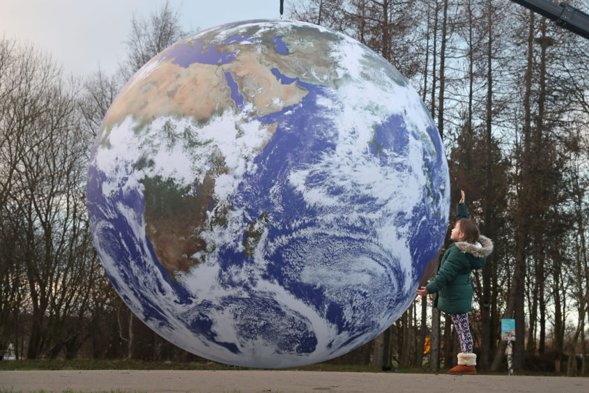 A young girl looks at Gaia, a seven-metre scale model of Earth.