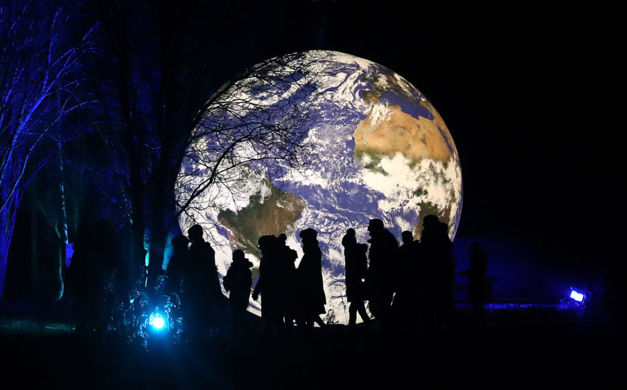 Visitors walks past the art installation Gaia, a seven-metre scale model of Earth created by artist Luke Jerram.