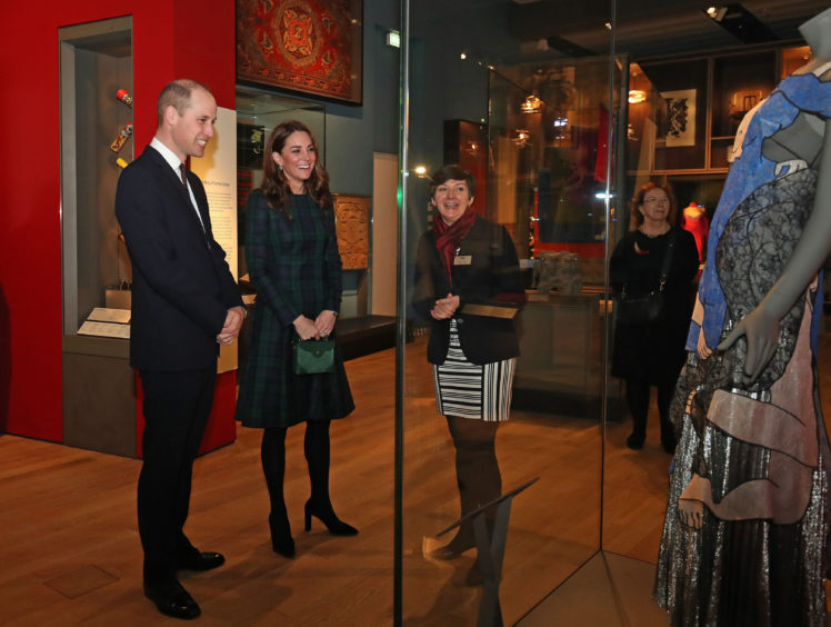 The Duke and Duchess with Senior Curator Joanna Norman look at a Christopher Kane dress. Jane Barlow/PA Wire