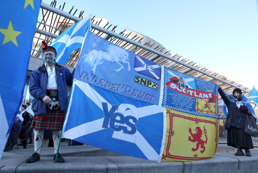 A campaigner holds a banner at an Independence demonstration outside the Scottish Parliament in Edinburgh in 2019.