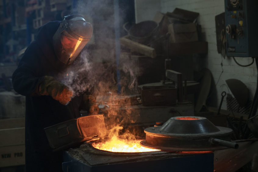 A member of staff checks on the temperature of the furnace  during the hand-made casting.