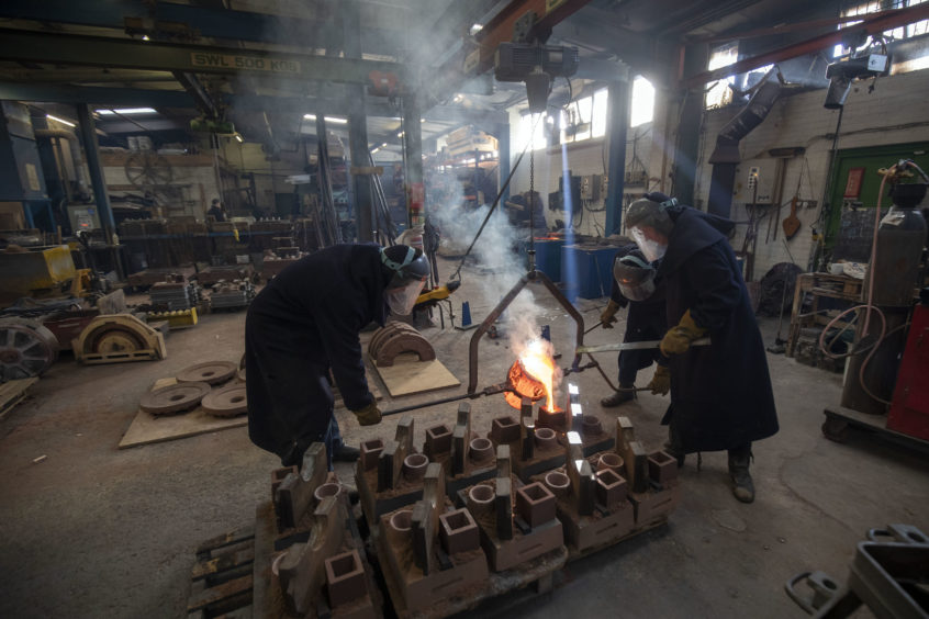Hot bronze metal is poured into the sand casts.
