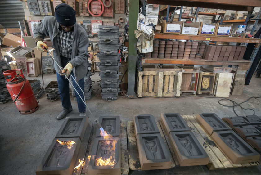 Rupert Francis sets fire to the sand casts as they are prepared for the metal to be poured into them during the hand-made casting.